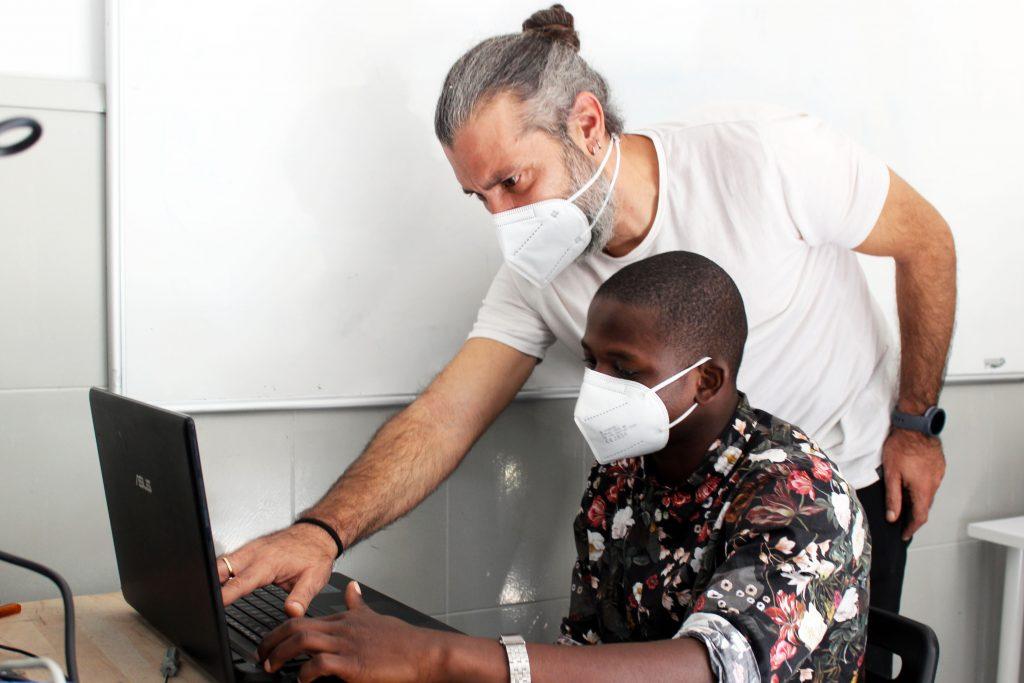 Educador i jove al taller de reparació d'ordinadors de la Fundació Marianao