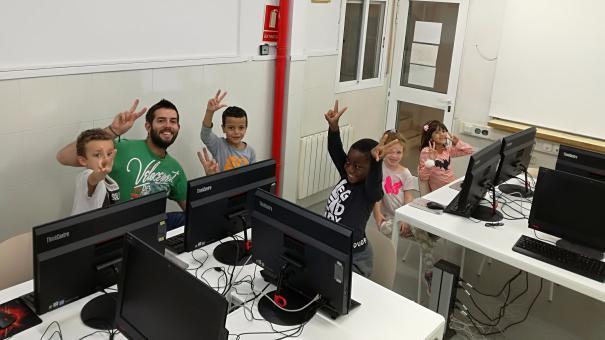 Grup d'infants del Casal Infantil fent classe de programació